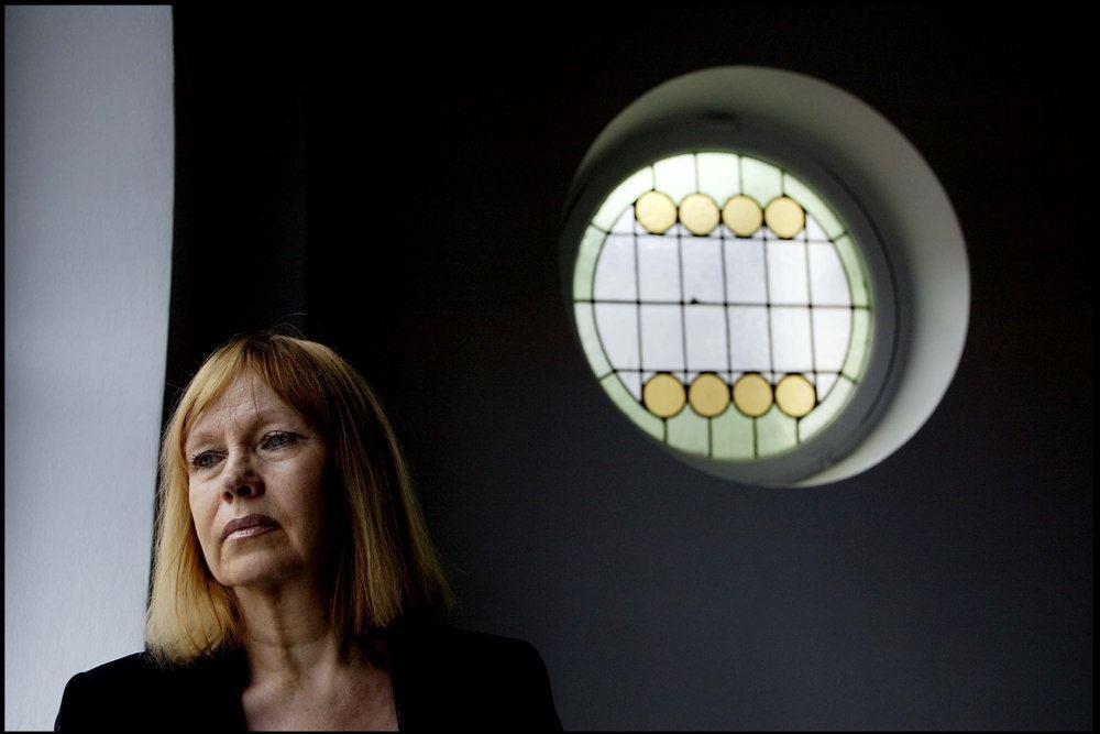 En rødhåret dame ved et rundt vindue