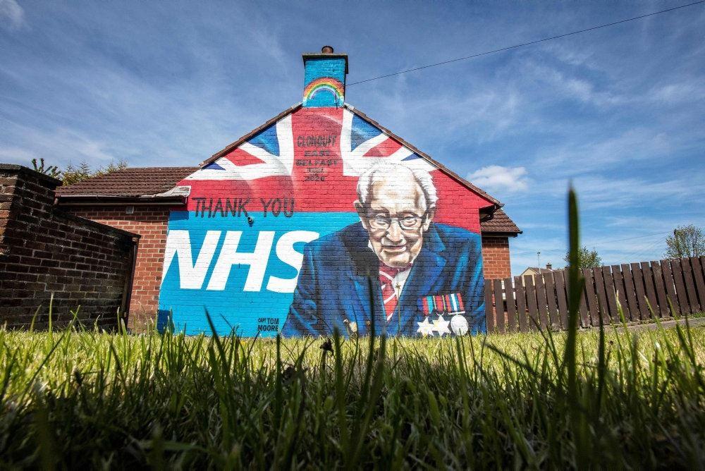 en mand malet på en gavl med et NHS bagved