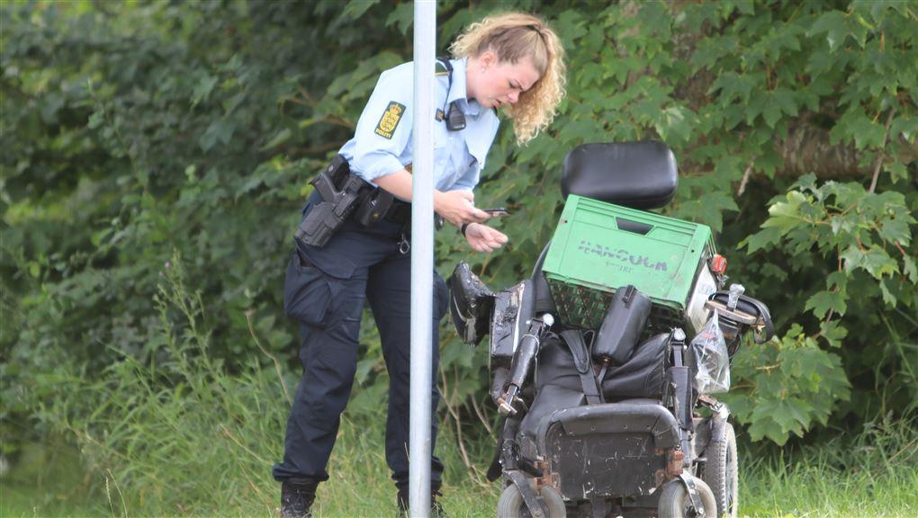 betjent undersøger kørestol