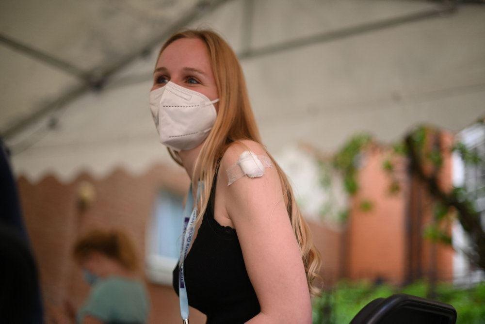 kvinde med mundbind venter på at få vaccination