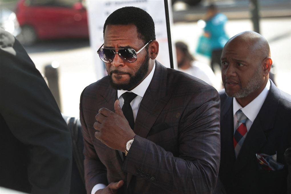 mand iført solbriller og slips ankommer til retssal