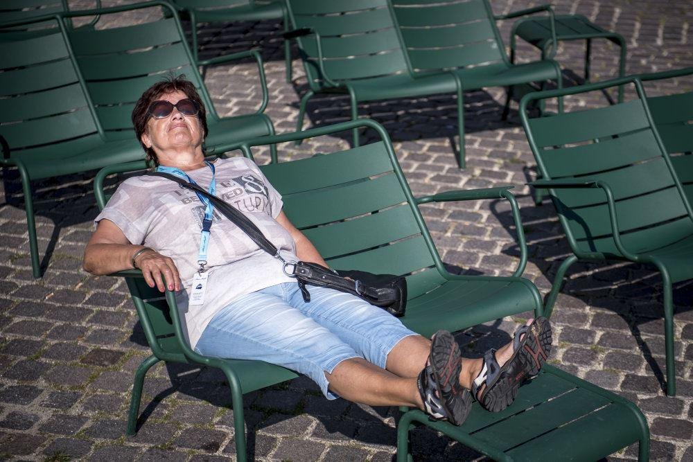 kvinde med solbriller slapper af på bænk