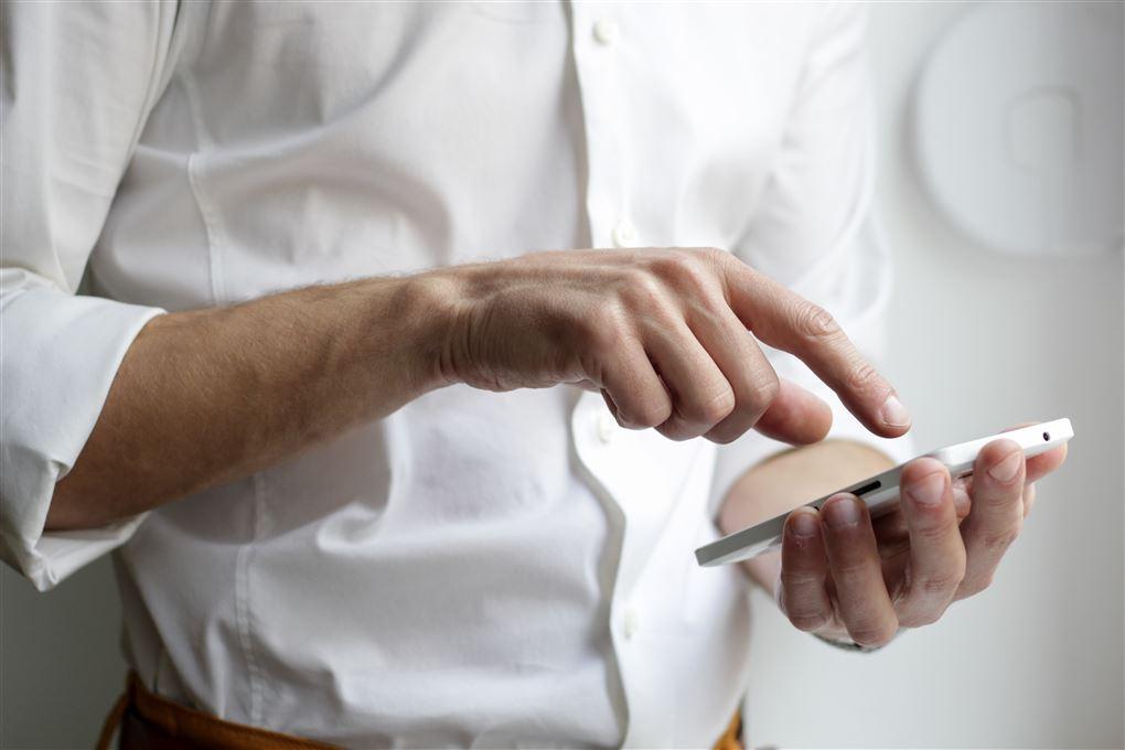 Mand står og taster på sin mobiltelefon