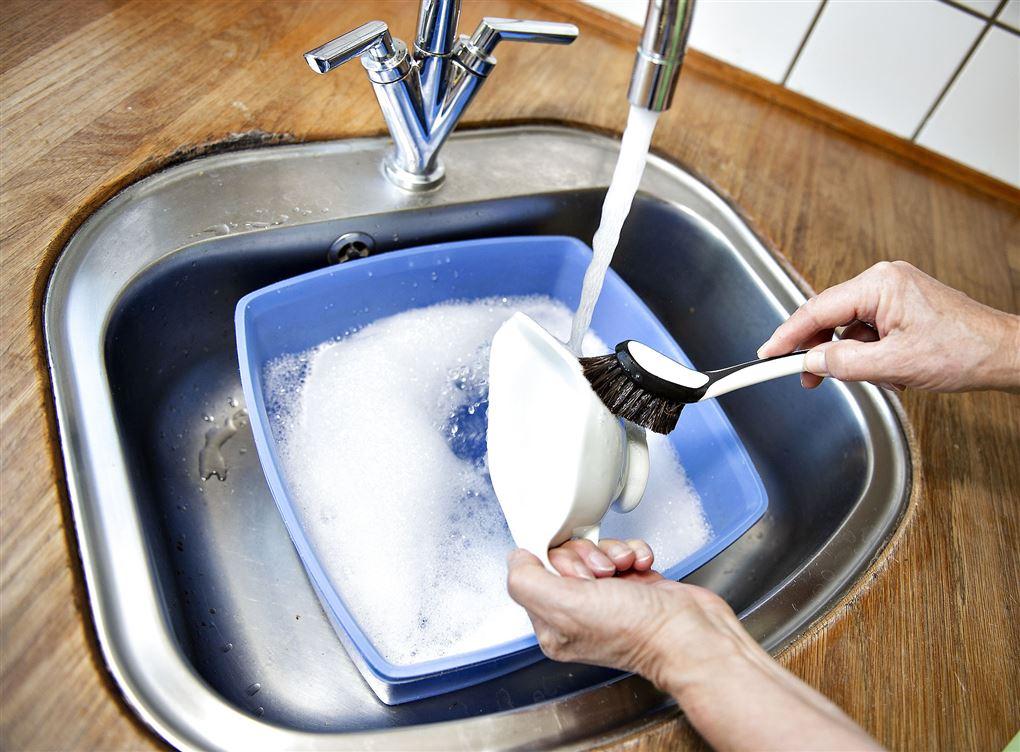 En som vasker op med en opvaskebørste