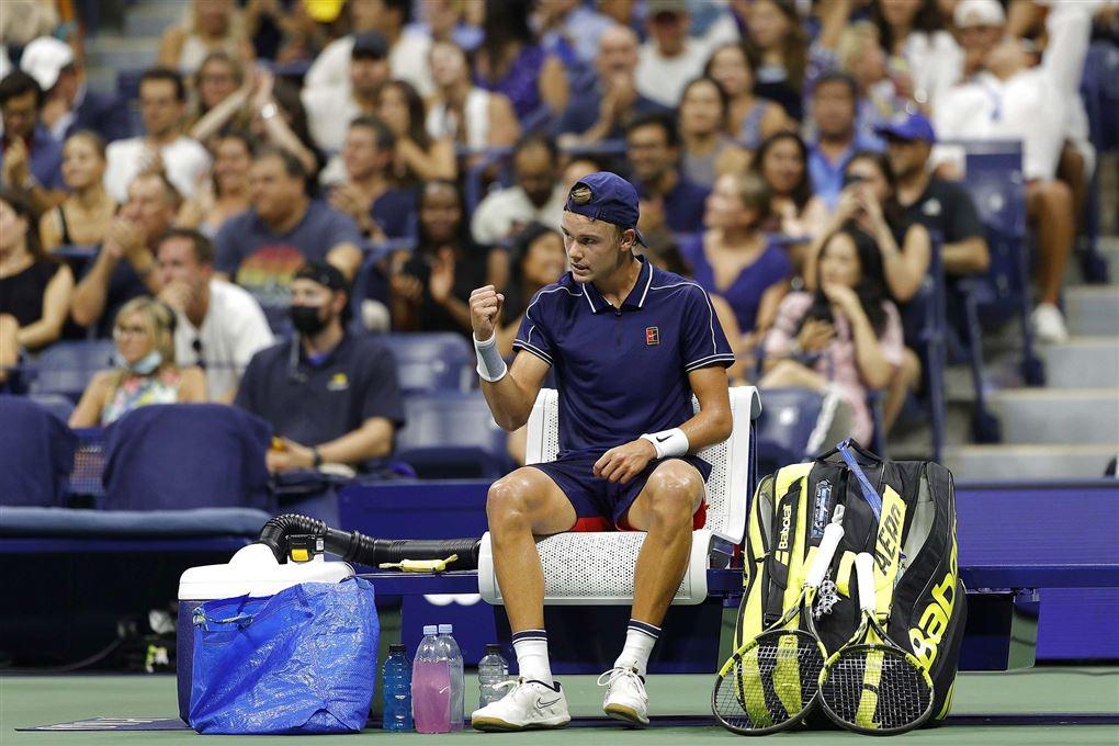 tennisspilelr sidder på stol under kamp med blå ikea-pose ved sin side