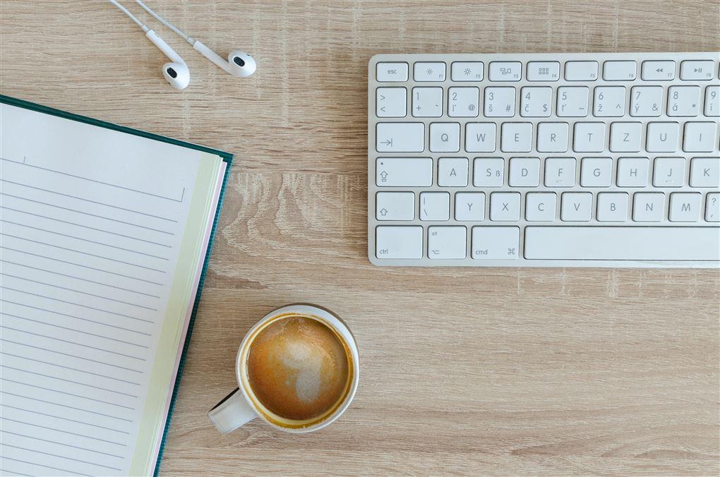 Et tastatur og en kop kaffe på et bord