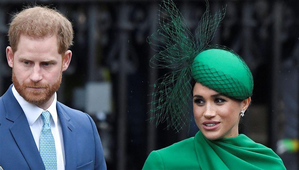 En mand i blåt jakkesæt og en kvinde i grønt outfit med hat