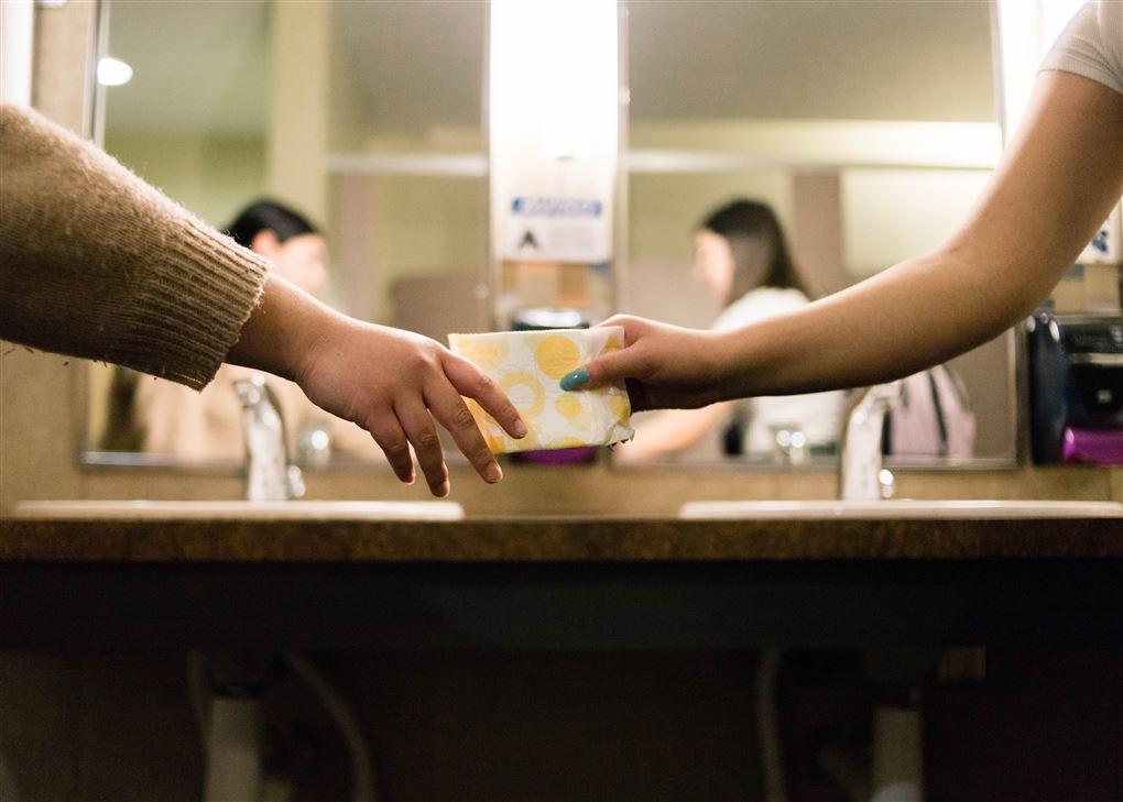 en hånd rækker et bind til en anden hånd på et toilet.