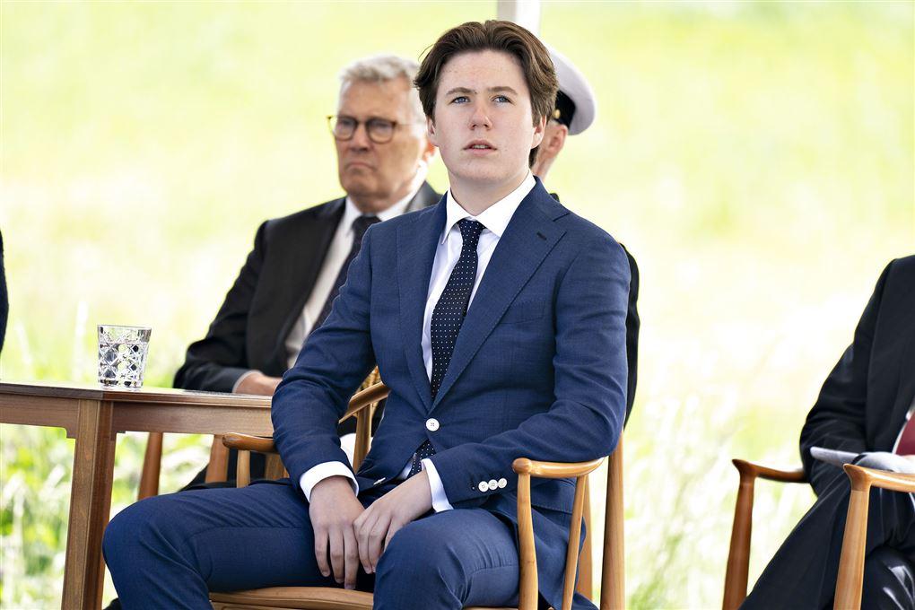 Prins Christian i mørkeblåt jakkesæt. Han sidder på en stol.