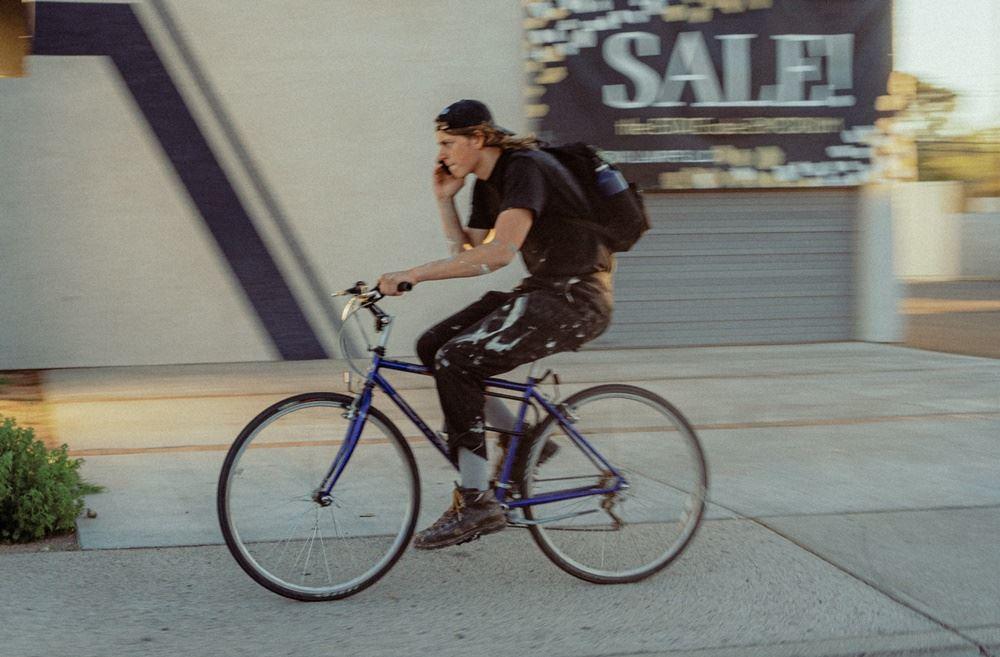 mand kører på cykel og taler i mobiltelefon samtidig
