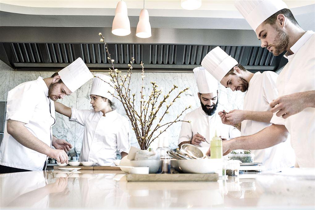 Mange fine kokke omkring et firkantet bord med mad