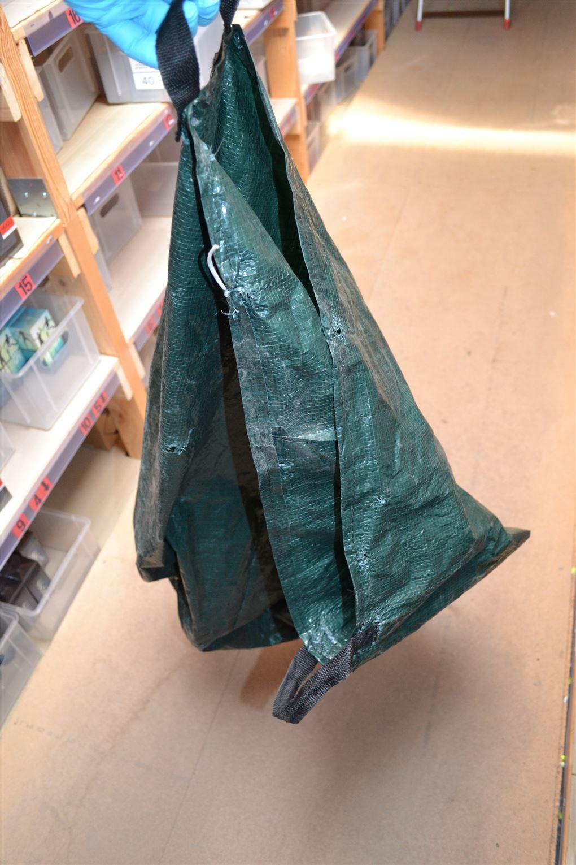 En mørkegrøn stor sæk lavet af en form for pressening.