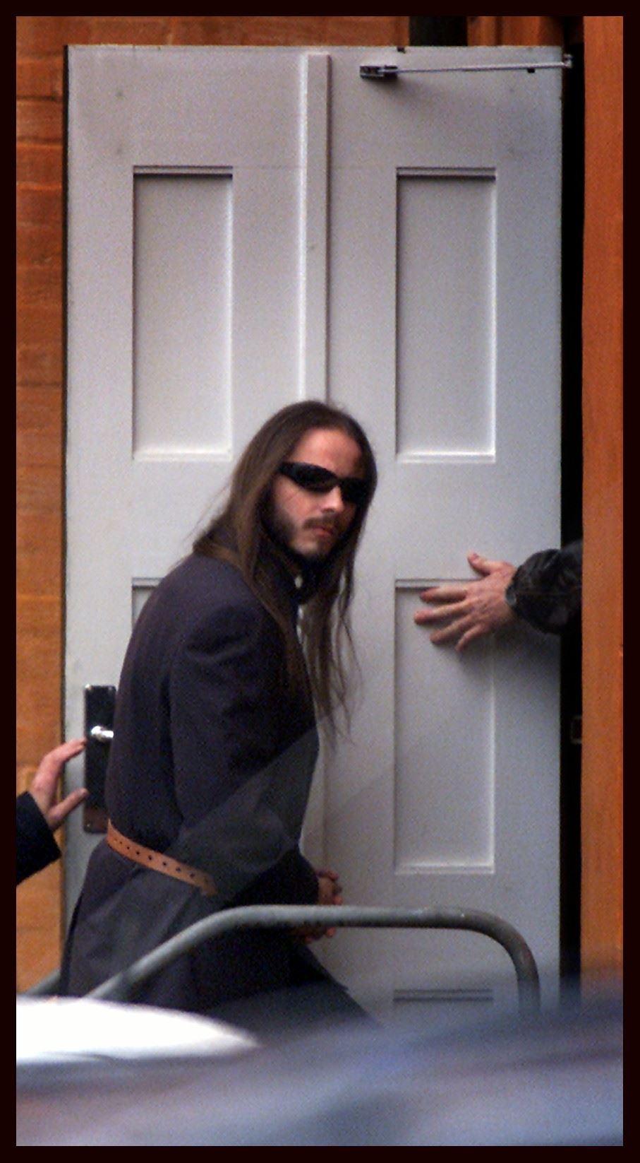 Peter Lundin på vej i retten med langt udslået hår og solbriller.