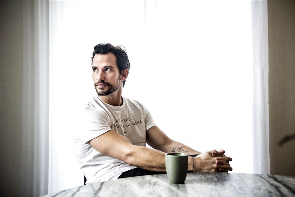 En mand med skæg ved et bord og en kop på bordet