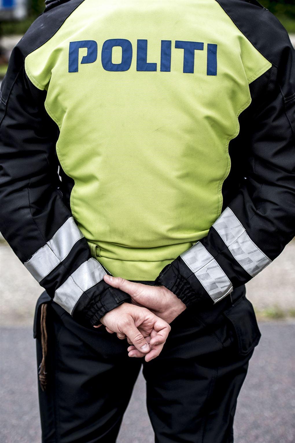 En politibetjent set fra ryggen.