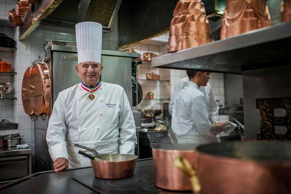 en kok med høj kokkehat i et køkken med mange kobbergryder