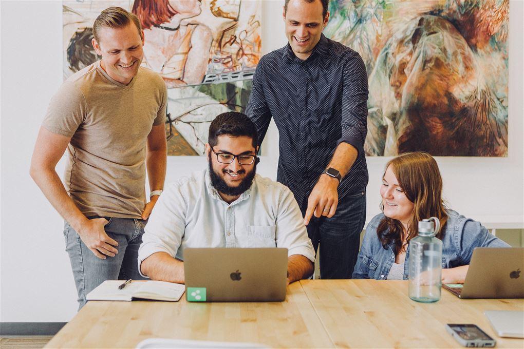 5 yngre smilende mennesker omkring en computer