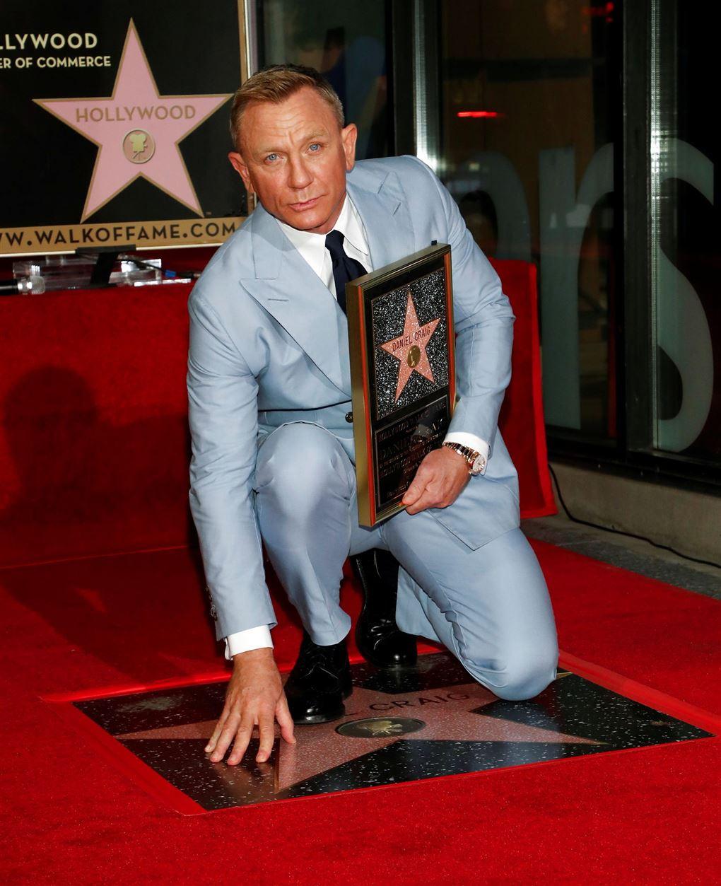 En mand i lyseblåt jakkesæt med en stjerne skilt i hånden