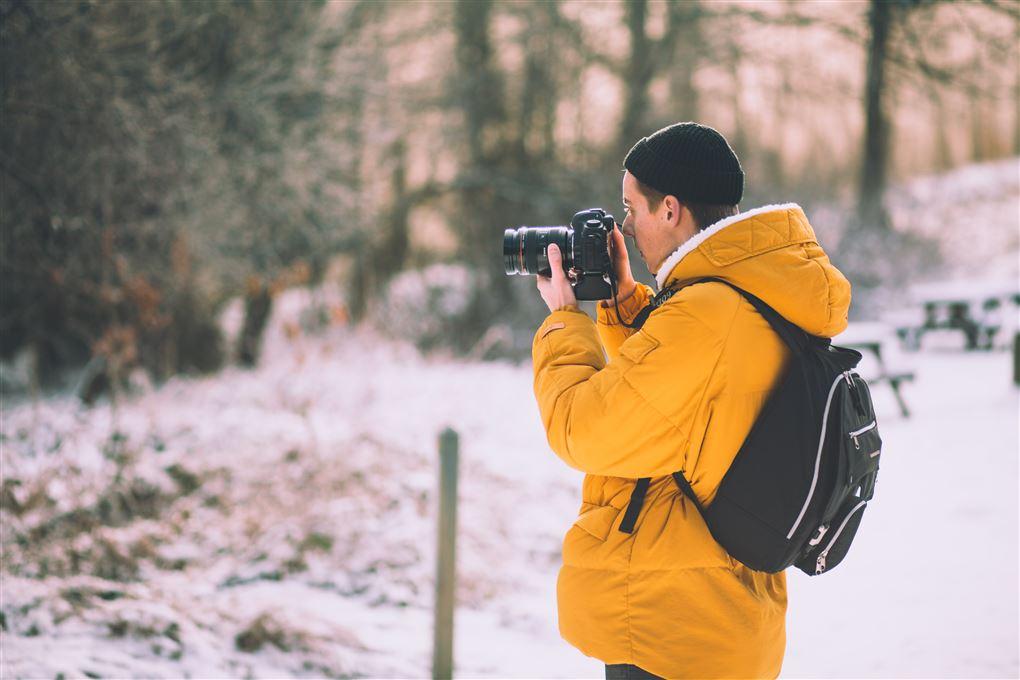En mand fotograferer i en sneklædt skov