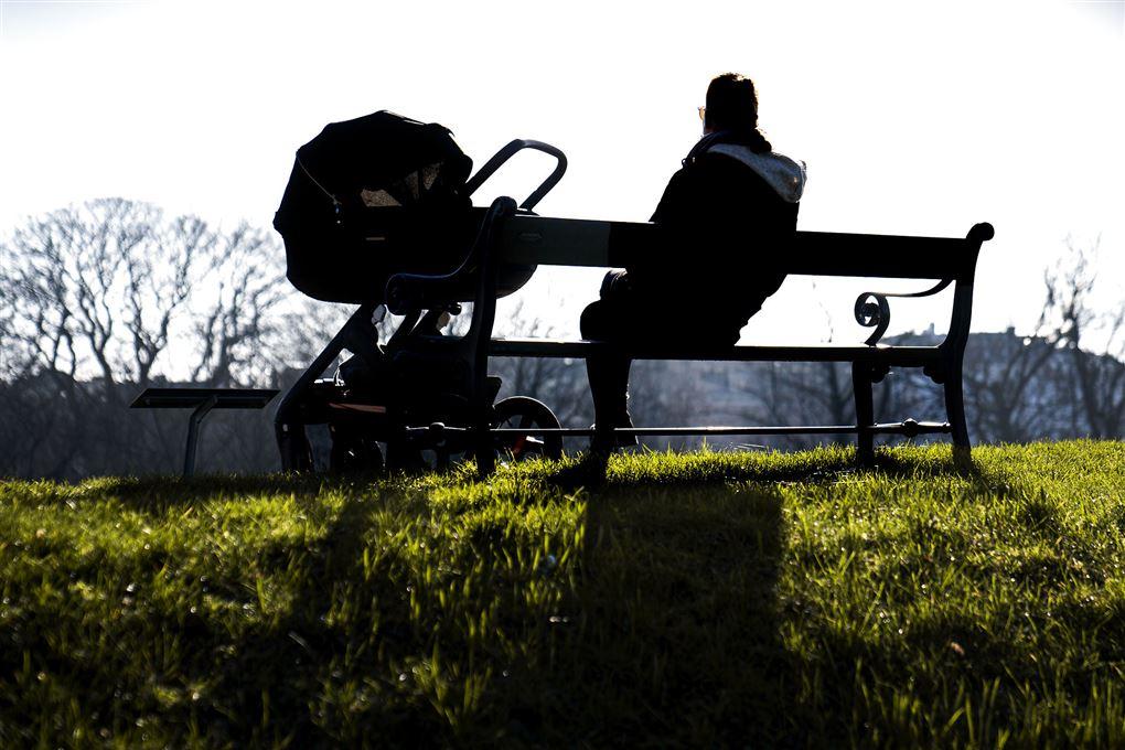 person sidder på bænk ved siden af barnevogn