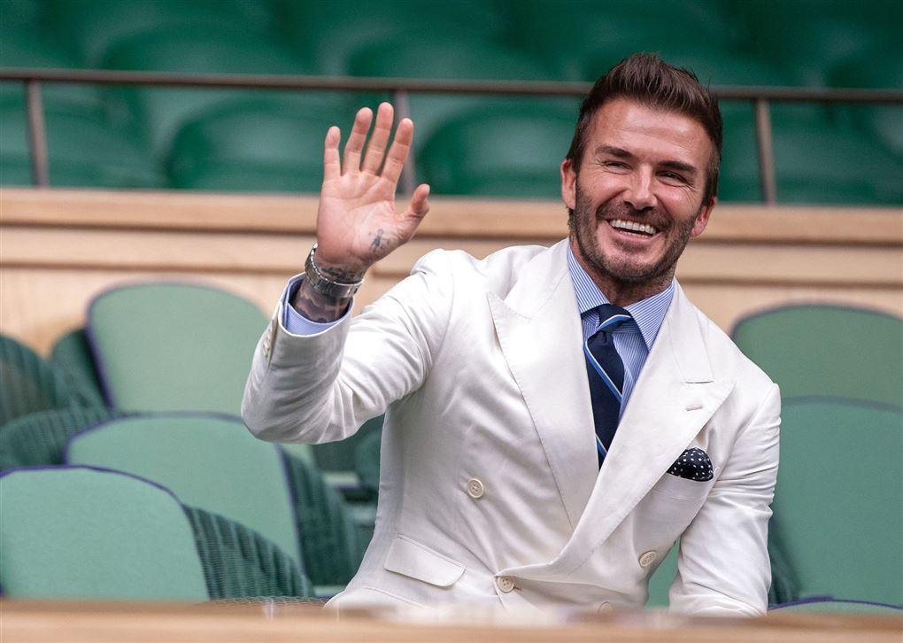 En mand i hvidt jakkesæt griner og vinker