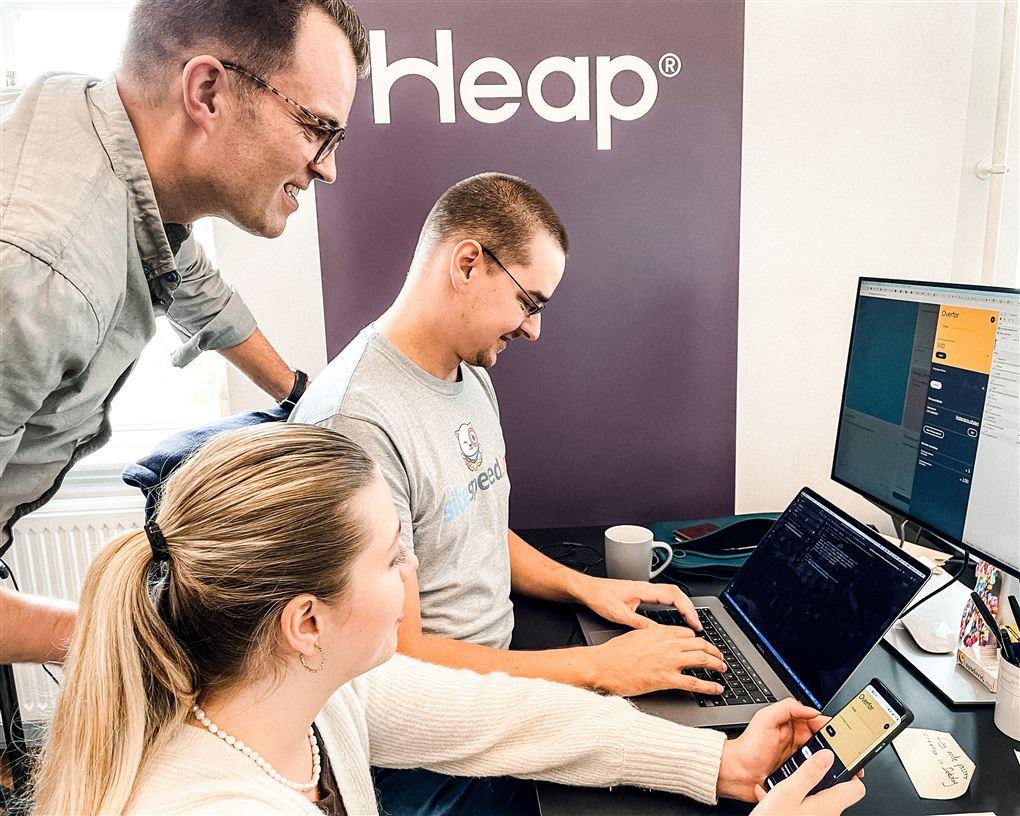 Tre mennesker omkring en computer