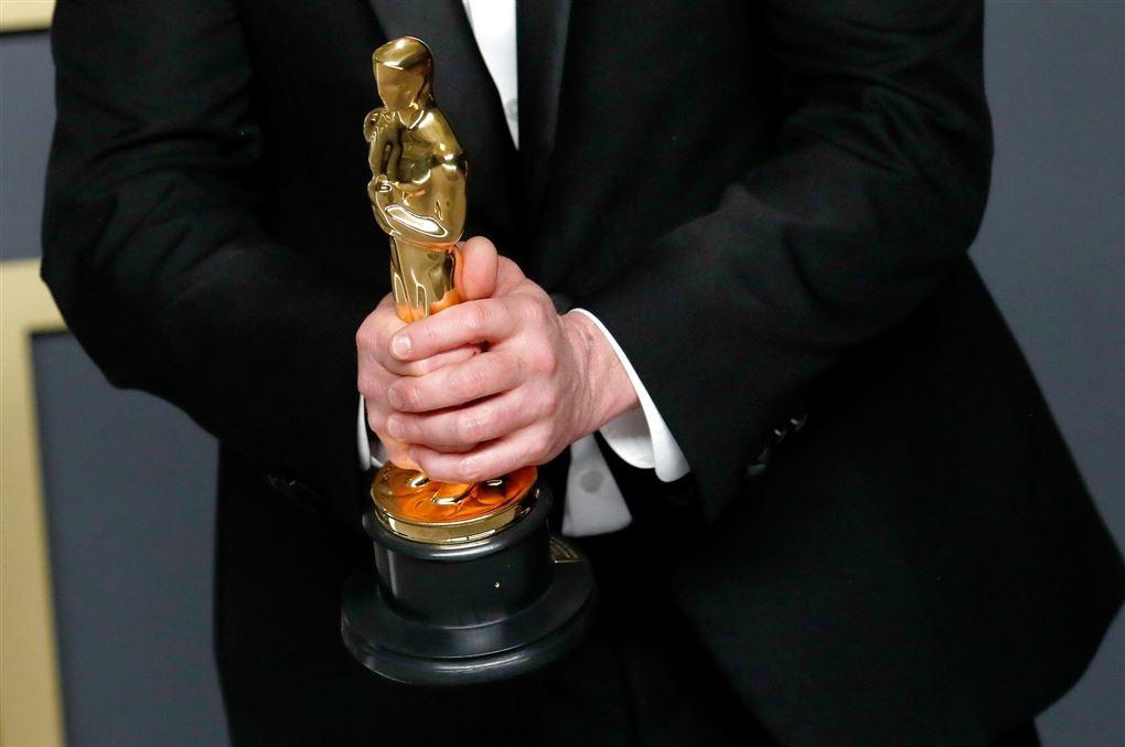 En mand med en Oscar statuette mellem begge hænder.