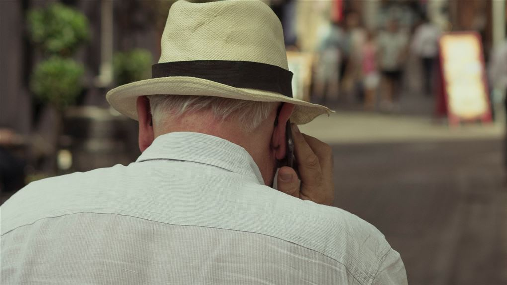 En ældre mand set bagfra med en mobil ved øret