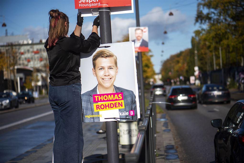 En kvinde hænger valgplakat op i en lygtepæl, hvor også Thomas Rhodens valgplakat hænger